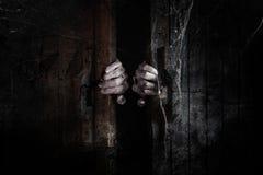 As mãos de Ghost abrem a porta de madeira do interior da sala escura velha imagem de stock royalty free