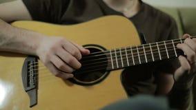As mãos de homem novo que jogam a guitarra acústica vídeos de arquivo