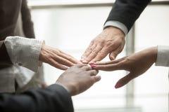 As mãos de quatro sócios diversos juntam-se junto, perto acima da vista Imagem de Stock Royalty Free