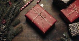 As mãos de Santa Claus puseram para dar o presente grande do ano novo sobre o fundo de madeira do estilo com a decoração do ano n filme