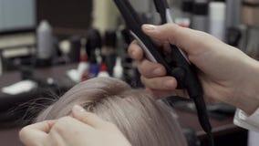 As mãos de um cabeleireiro da menina para fazer a denominação para o cabelo video estoque