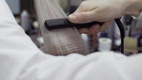 As mãos de um cabeleireiro da menina para fazer a denominação para o cabelo filme