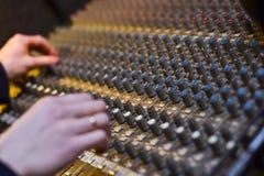 As mãos de um DJ no fundo, musical audio profissional Imagem de Stock