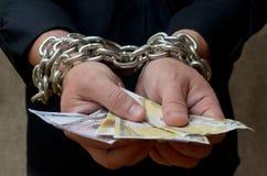 As mãos de um homem limitam por uma corrente e dinheiro guardar Sujeição do crédito fotos de stock royalty free