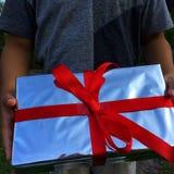 As mãos de um menino estão guardando uma caixa de presente foto de stock royalty free