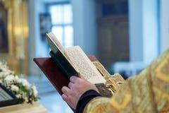As mãos de um padre ortodoxo, de uma cruz e de um livro de oração foto de stock