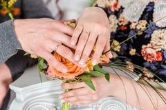 As mãos de um par novo-casado com alianças de casamento foto de stock