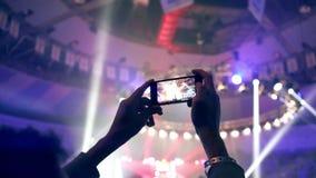 As mãos de um tiro do homem novo iluminam-se em um concerto com seu smartphone filme