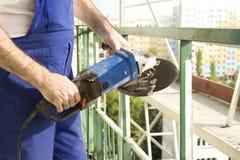 As mãos de um trabalhador da construção estão guardando uma grande ferramenta elétrica moedor Barreira do aço do corte Imagens de Stock