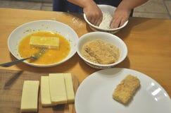 As mãos de uma criança em idade pré-escolar estão revestindo fatias de queijo nos ovos, na farinha e nas côdeas de pão ralado Fotos de Stock
