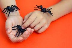 As mãos de uma criança que joga com as aranhas de borracha pretas brincam no fundo de papel alaranjado Conceito de Dia das Bruxas fotografia de stock