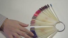 As mãos de uma menina em um salão de beleza escolhem o tratamento de mãos futuro em uma paleta de cores vídeos de arquivo