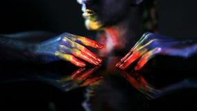 As mãos de uma menina de incandescência de pele escura com cor preparam filme