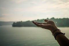 As mãos de uma menina que esteja jogando a chuva Fotografia de Stock