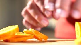 As mãos de uma mulher com uma faca cortaram uma cenoura com uma faca em uma placa de desbastamento de madeira em uma cozinha home filme