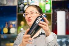 As mãos de uma mulher do barman guardam um abanador profissional fotografia de stock