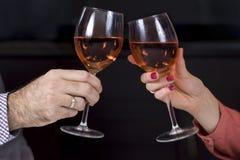As mãos de uma mulher e de um homem com vidros de vinho nas mãos estão brindando Vidros de vinho com um fundo escuro fotos de stock