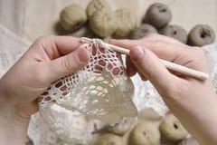 As mãos de uma mulher fazem malha um vestido branco, linha fotografia de stock