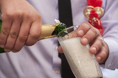 As mãos derramam o champanhe Foto de Stock