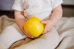 As mãos do bebê dois guardam a maçã amarela As mãos da criança e opinião dianteira de fruto fresco Dieta colocada lisa e conceito fotografia de stock