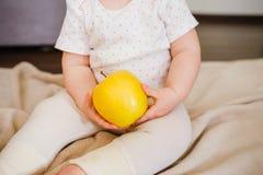As mãos do bebê dois guardam a maçã amarela As mãos da criança e opinião dianteira de fruto fresco Dieta colocada lisa e conceito imagem de stock
