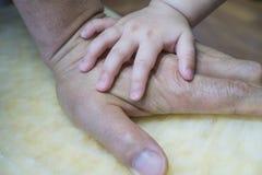 As mãos do bebê na mão do avô fotografia de stock