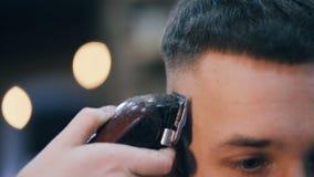 As mãos do cabeleireiro cortam a cabeça do ` s do indivíduo por uma tosquiadeira vídeos de arquivo