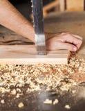 As mãos do carpinteiro que cortam a prancha com serra de fita Fotos de Stock