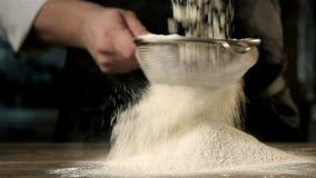 As mãos do chefe que peneiram a farinha através de uma peneira para cozer vídeos de arquivo