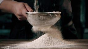 As mãos do chefe que peneiram a farinha através de uma peneira para cozer filme