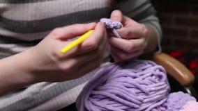As mãos do close-up com agulhas de confecção de malhas, mulher bonita fazem malha video estoque