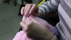 As mãos do close up com agulhas de confecção de malhas, mulher fazem malha filme