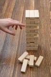 As mãos do close-up do homem retiram tijolos de madeira Fotos de Stock Royalty Free