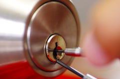 As mãos do close up do serralheiro que usam o metal escolhem ferramentas para abrir a porta fechado Imagem de Stock