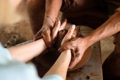 As mãos do close up do oleiro e de seu aprendiz novo criam um vaso em uma roda de giro do ` s do oleiro Foto de Stock