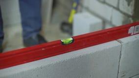 As mãos do construtor puseram o nível de bolha sobre a parede recentemente construída para verificar sua regularidade video estoque