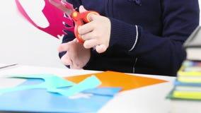 As mãos do corte da menina dão forma do papel colorido para ofícios video estoque