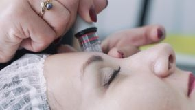 As mãos do cosmetologist do close-up fazem procedimentos na cara paciente com hidro dispositivo de descascamento, movimento lento video estoque