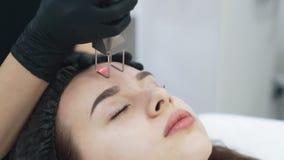As mãos do cosmetologist do movimento lento fazem à casca facial da menina com dispositivo especial filme