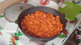 As mãos do cozinheiro branco adicionam a cenoura do corte e espalham-na sobre a cebola ao cozinhar o domlyam vídeos de arquivo