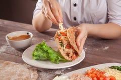 As mãos do cozinheiro chefe encheram tacos Imagem de Stock
