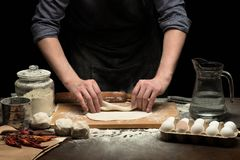 As mãos do cozinheiro chefe estão fazendo um rolo da massa foto de stock royalty free