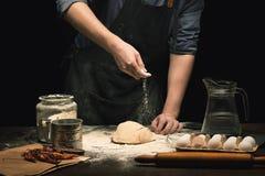 As mãos do cozinheiro chefe estão polvilhando um pó da farinha na massa fotos de stock royalty free