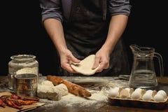 As mãos do cozinheiro chefe estão preparando uma massa imagens de stock royalty free