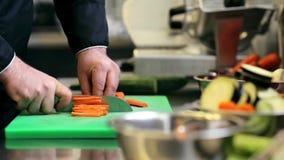 As mãos do cozinheiro chefe masculino cozinham o desbastamento da cenoura na cozinha video estoque