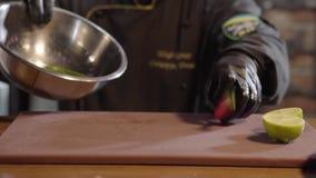 As mãos do cozinheiro chefe puseram a pimenta verde e vermelha com o limão cutted no fim de alumínio grande da bacia acima Homem  video estoque