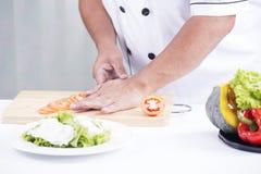As mãos do cozinheiro chefe que cortam o tomate Fotografia de Stock