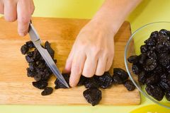 As mãos do cozinheiro estão cortando a ameixa seca Fotos de Stock Royalty Free