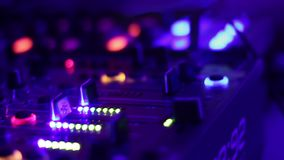 As mãos do disco-jóquei que empurram e que giram botões no console de mistura nightclub video estoque