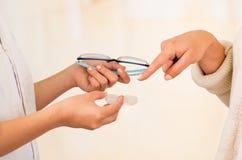 As mãos do doutor de Femalee que dão vidros e lente de contato à escolha de oferecimento paciente, paciente escolhem a lente de c fotografia de stock royalty free
